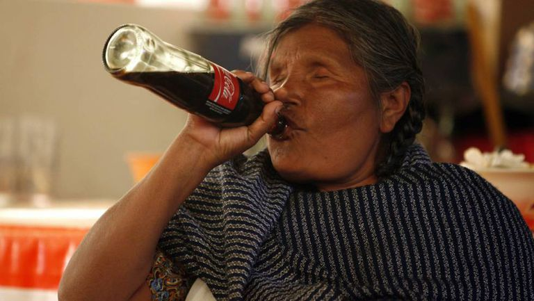 A Mazahua woman drinking Coca-Cola.