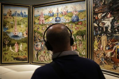 A visitor admires 'The Garden of Earthly Delights' by Hieronymus Bosch.