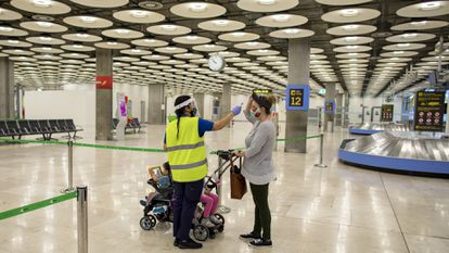 A traveler arriving in Madrid's Barajas Airport last summer has her temperature checked.