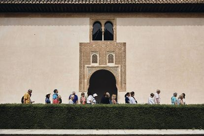 Gardeners work under the gaze of the 8,000 tourists who visit every day.