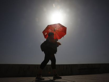A woman shades herself from the sun in Córdoba in Andalusia.