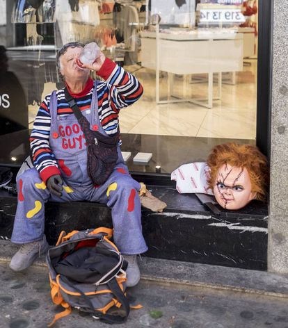 Juan, dressed as Chucky, takes a rest in front of a shop.