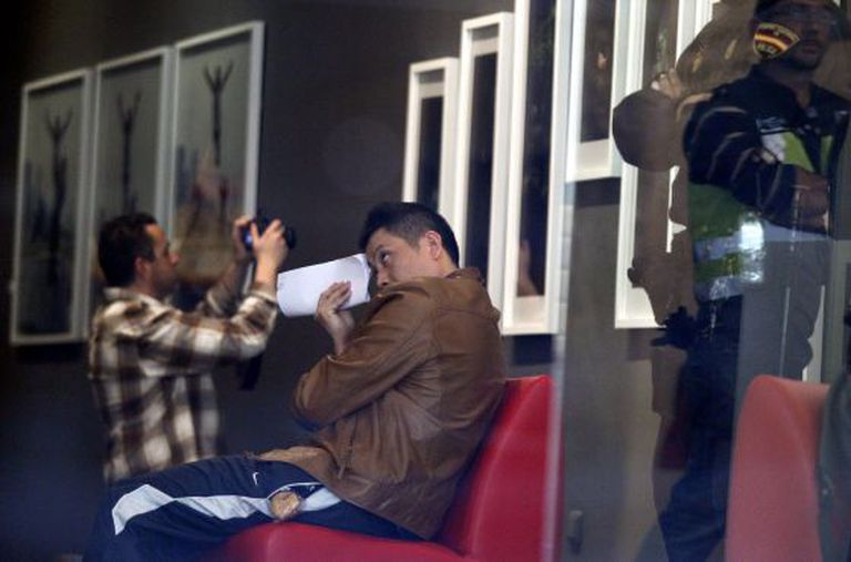 Gao Ping, wearing a brown jacket, looks away as police raid his Madrid art gallery on Tuesday.
