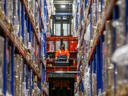 A worker places boxes filled with vaccines in a logistics center in Leganés in Madrid.