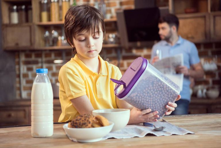 A child pouring out breakfast cereal.