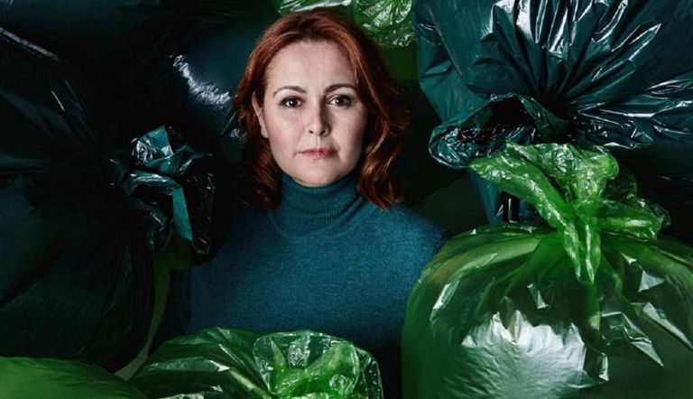 María Gallay surrounded by trash bags.