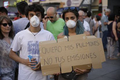 """Protesters with a sign reading: """"I want my lungs, not your emissions."""""""