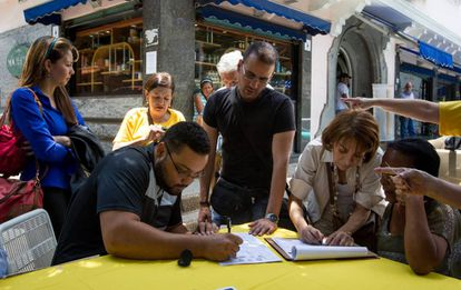 Opponents of President Nicolás Maduro sign the petition for a recall referendum.