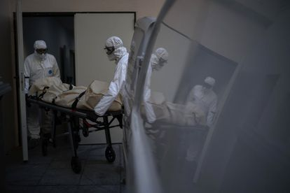 Two workers remove the body of a coronavirus victim from a seniors residence in Barcelona.