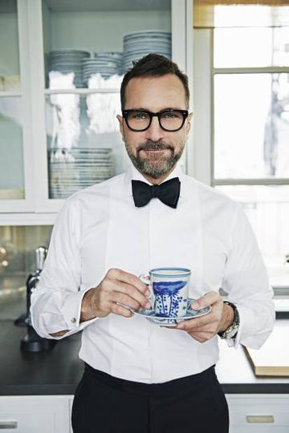 """James Costos wearing MANUEL CALVO DE MORA shirt and pants, TURNBULL & ASSER bow tie, IWC watch, SHURON glasses, GIVENCHY shoes and vintage cuff-links, which were a gift from his partner, the interior decorator Michael Smith. """"I like to honor and promote the tradition of Spanish tailoring. A lot of fashion from Spain has entered my wardrobe,"""" he explains in his kitchen."""