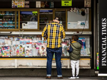 A man with his son at a newsstand by La Paz hospital, in Madrid.