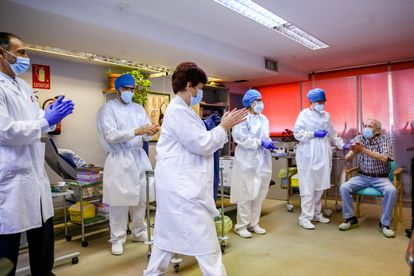 Healthcare workers applaud Nicanor, 72, after he became the first man to receive the Covid-19 vaccine in the Madrid region on Sunday.