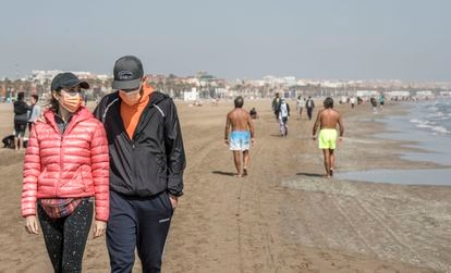 People walking down a beach in Valencia on March 31.