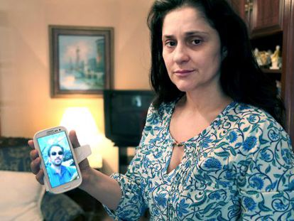 Julia Ordóñez, wife of police inspector José Antonio Martínez, who died on Sunday, holds up a cellphone image of her husband.