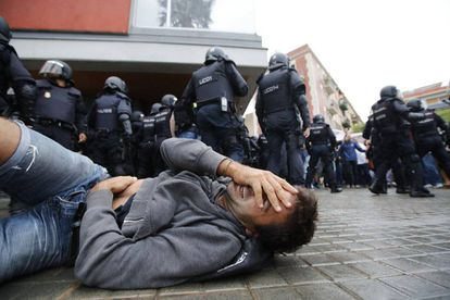 A man falls to the floor during an operation by Spanish National Police riot officers at the Mediterránea de la Barceloneta school, Barcelona.