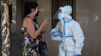 A woman speaks with a health worker in Ripollet, in Barcelona province, where the Catalan region government has begun a mass Covi-19 testing campaign.