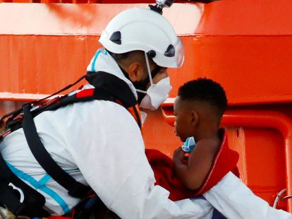 A migrant child is taken off a Spanish Coast Guard vessel in the port of Arguineguin, on the island of Gran Canaria.