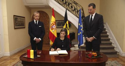 Queen Letizia signs a book of condolence in the presence of King Felipe (right) and the Belgian ambassador.