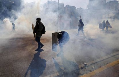 Anti-government protesters shielded themselves from tear gas canisters at a street protest in Caracas on Thursday.