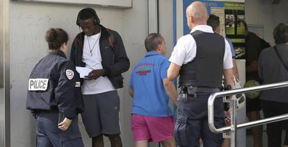 Two French police officers intercept a migrant at the border.