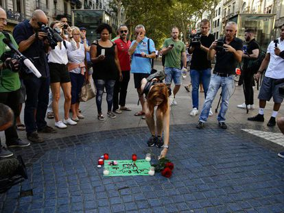 A woman lays flowers on La Rambla in tribute to the victims of the terrorist attacks in Catalonia.