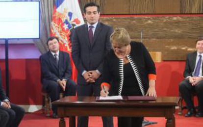 Rodrigo Peñailillo, standing behind President Bachelet, is in political hot waters.