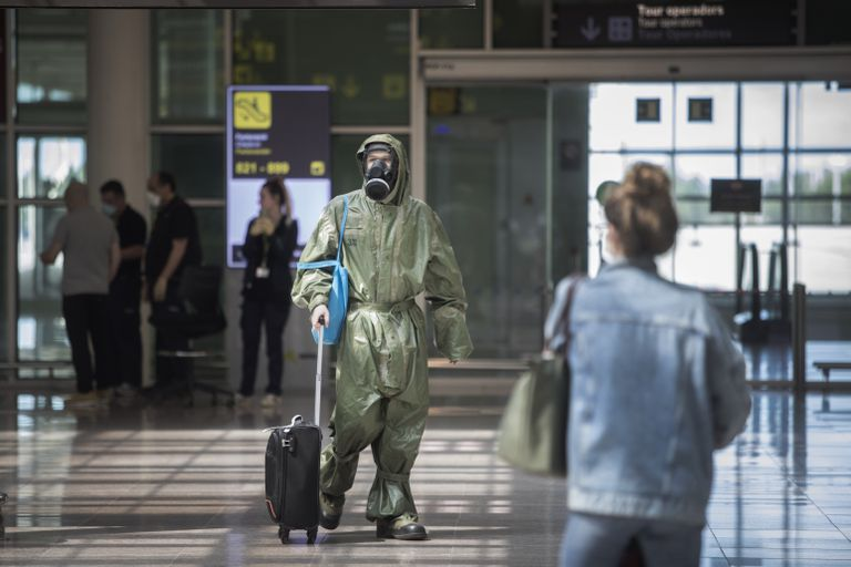 A passenger arrives from London in Barcelona's El Prat airport on Friday wearing military coveralls and a gas mask.