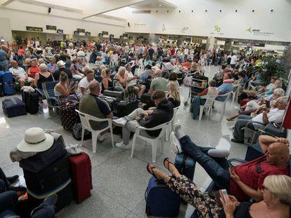 Tourists await their flights in Menorca airport.