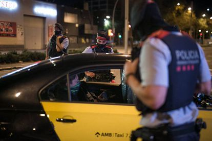 Catalan police officers at a curfew checkpoint in Barcelona on Sunday night.