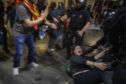 Police officers clash with demonstrators outside El Prat airport in Barcelona.