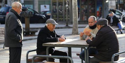 A group of men play cards in a street in Madrid.