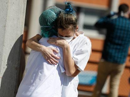 Two health workers hug outside the Severo Ochoa hospital in Leganés.
