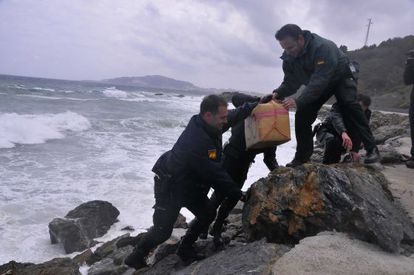 Civil Guard officers take one of the hashish packages out of the sea on Monday.