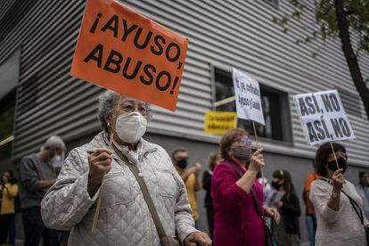 """A protester holds a sign with the message: """"Ayuso, abuse!"""" in reference to Madrid premier Isabel Díaz Ayuso."""