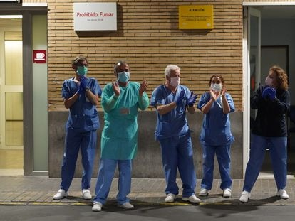 Health workers at a hospital in Seville applaud outside the emergency ward.