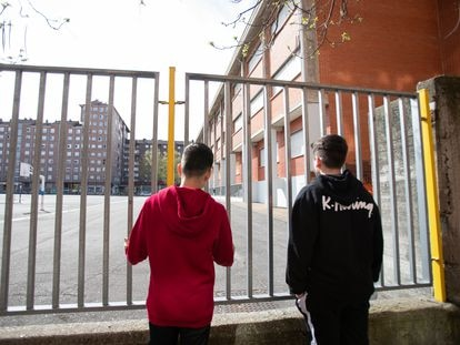 Two students look at a closed school in the Basque city of Vitoria during the coronavirus lockdown.