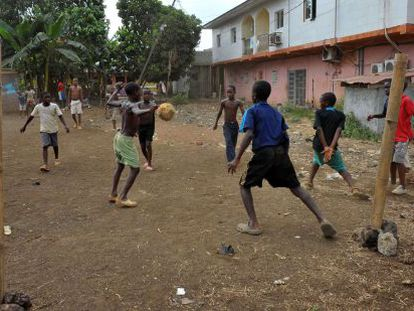 Young boys in Equatorial Guinea play football on a dry field in Malabo.