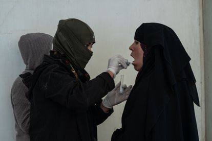 An SDF member collecting DNA samples from a woman at the section for Iraqi nationals inside Al-Hol camp.