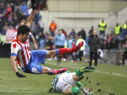 Atlético Madrid's Diego Costa falls under challenge from a Real Betis player.