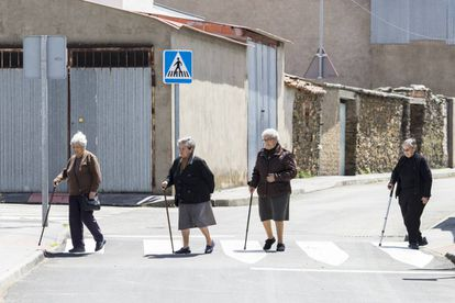 Four residents cross a street in Pescueza.