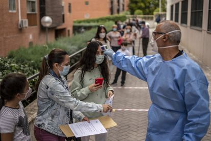 A health worker performs temperature checks in the Madrid district of Vallecas.