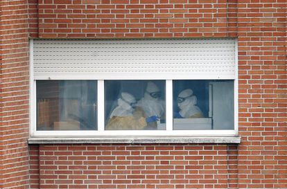 Health workers at Carlos III hospital wearing protective suits.