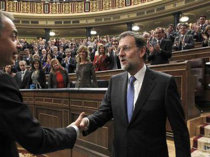José Luis Rodríguez Zapatero (l) congratulates Rajoy on his election as prime minister.