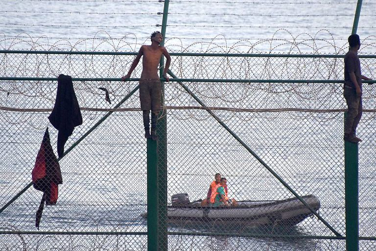 Migrants jump the border fence into Ceuta.
