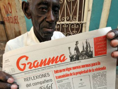 A Cuban man holds up a copy of state newspaper Granma.