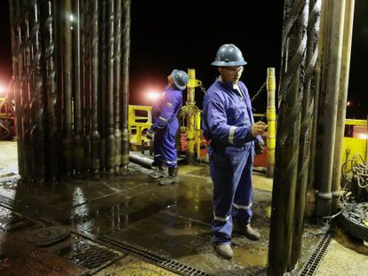 An operator works on an oil drill in Venezuela.