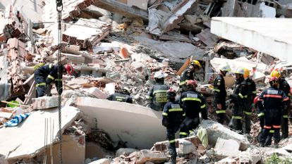 Fire fighters at the site of the collapse on Thursday.