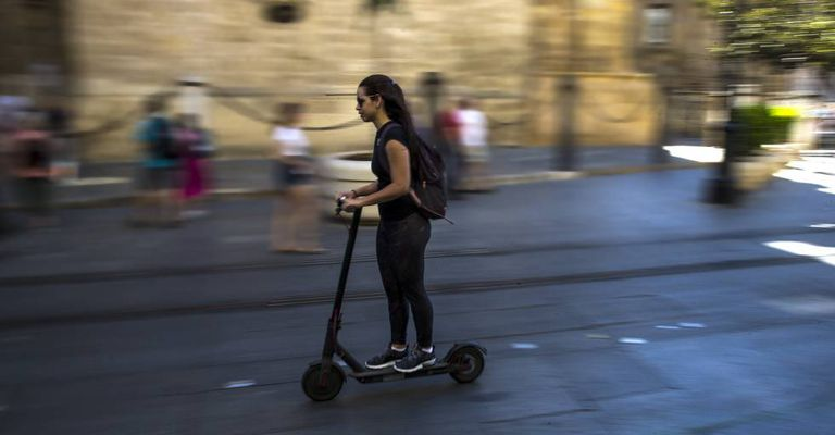 A young woman rides an electric scooter in Seville.