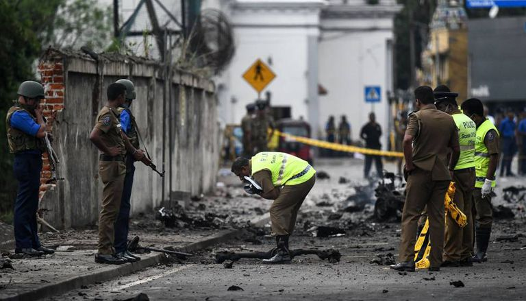 Security officers inspect the area where a bomb exploded in Colombo.