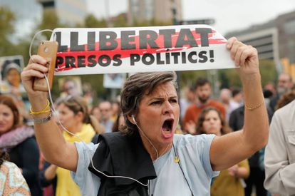 """A woman holds a a banner reading """"Freedom for political prisoners!"""""""